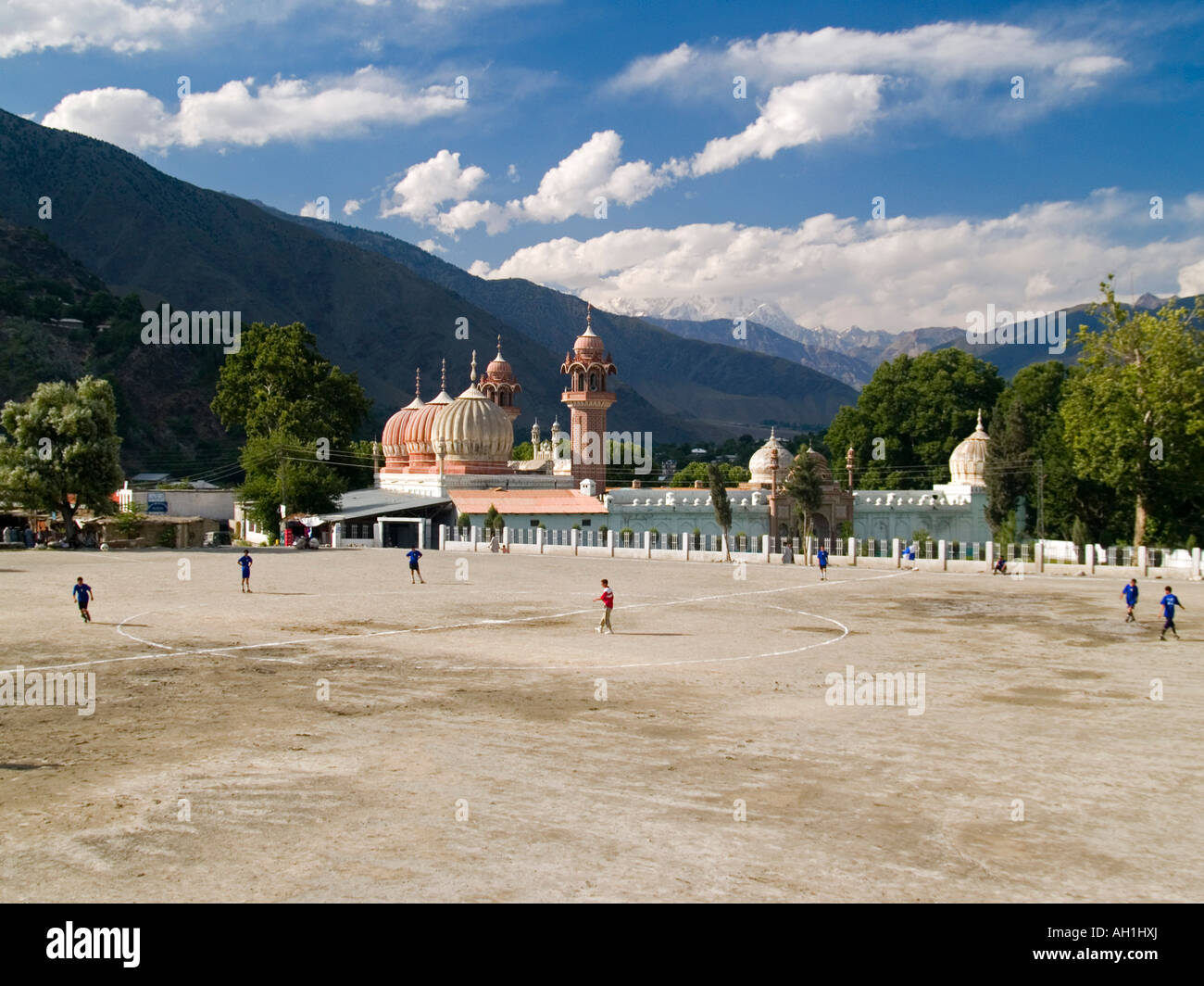 soccer game in front of the Shahi Mosque Chitral Pakistan with Trich Mir peak in the Hindu Kush rising behind - Stock Image