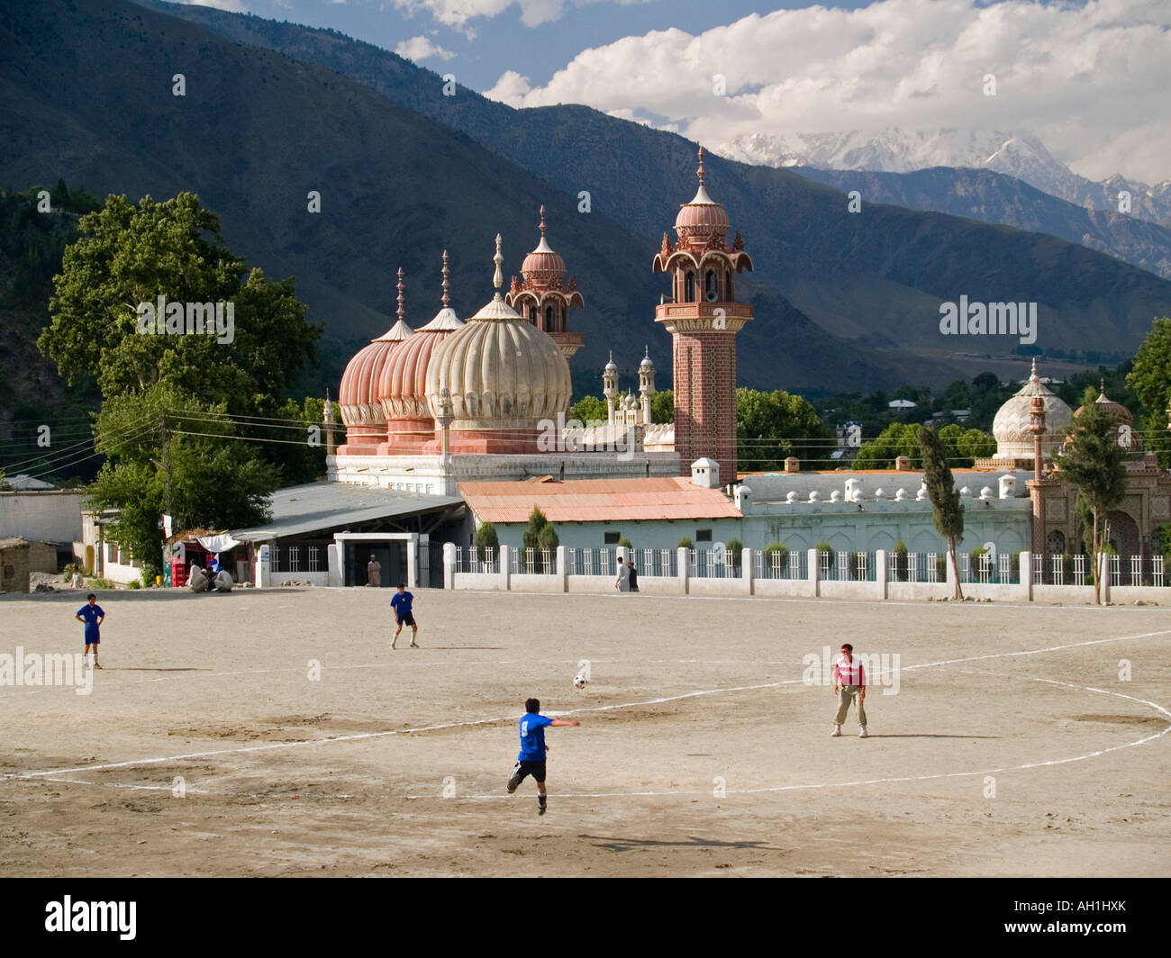 soccer game in front of the magical domes of the Shahi Mosque Chitral Pakistan with Trich Mir peak in the Hindu - Stock Image
