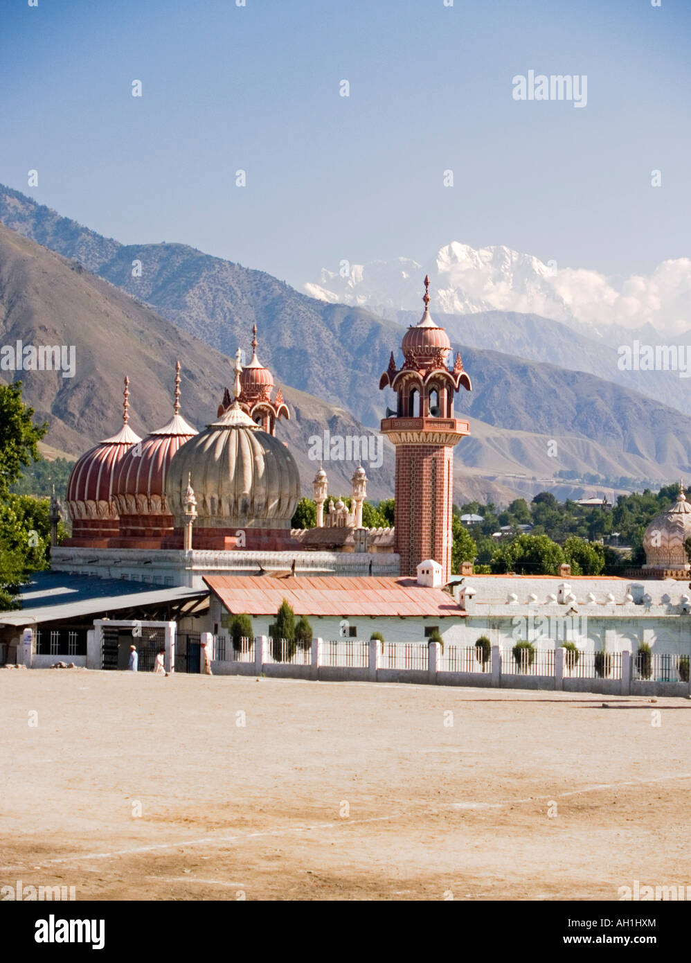 the surreal Shahi Mosque with Trich Mir peak in the Hindu Kush mountains towering behind it Chitral Pakistan - Stock Image