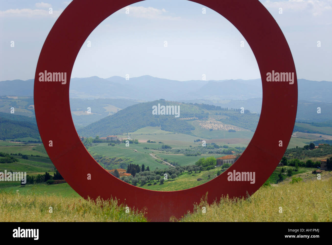 Large red circle iscupture n Tuscan countryside with view of Elsa Valley Italy - Stock Image