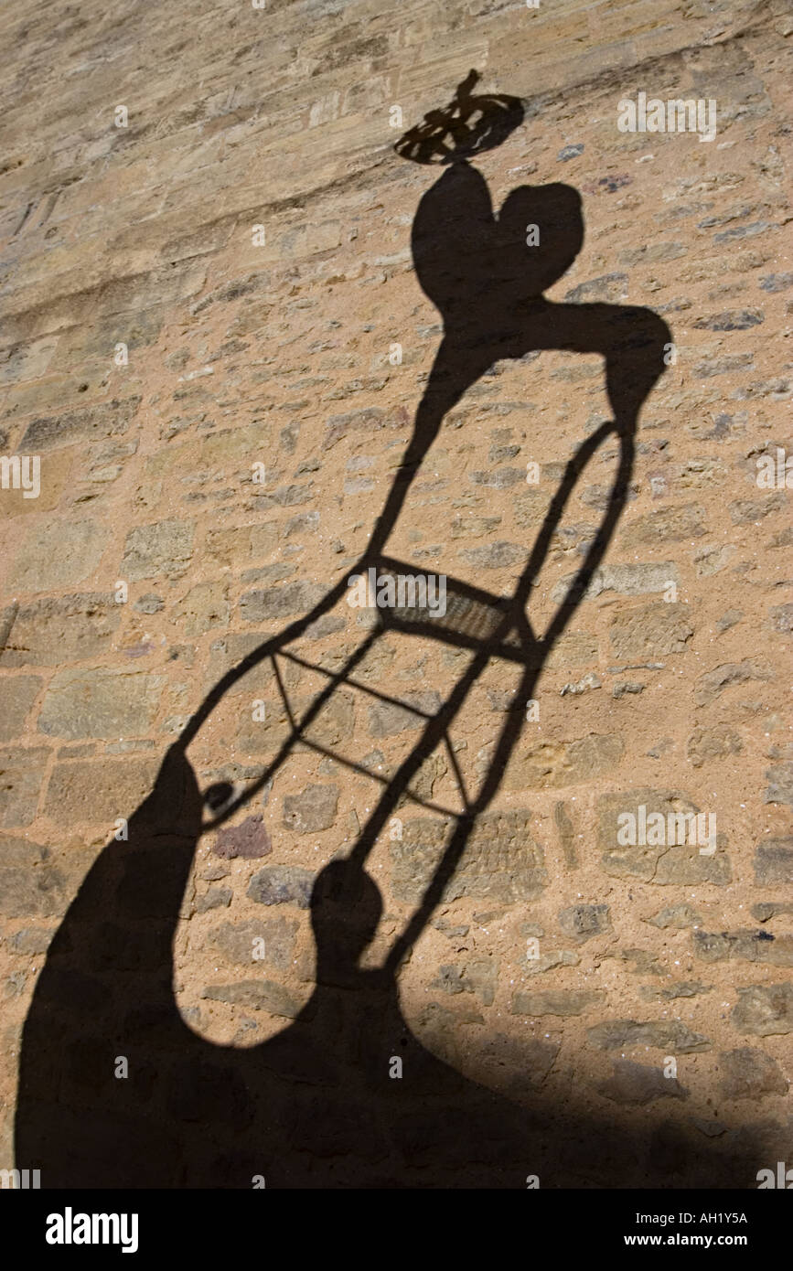 Shadows on a stone wall of stylised acrobats with chair Sarlat France 2005 - Stock Image