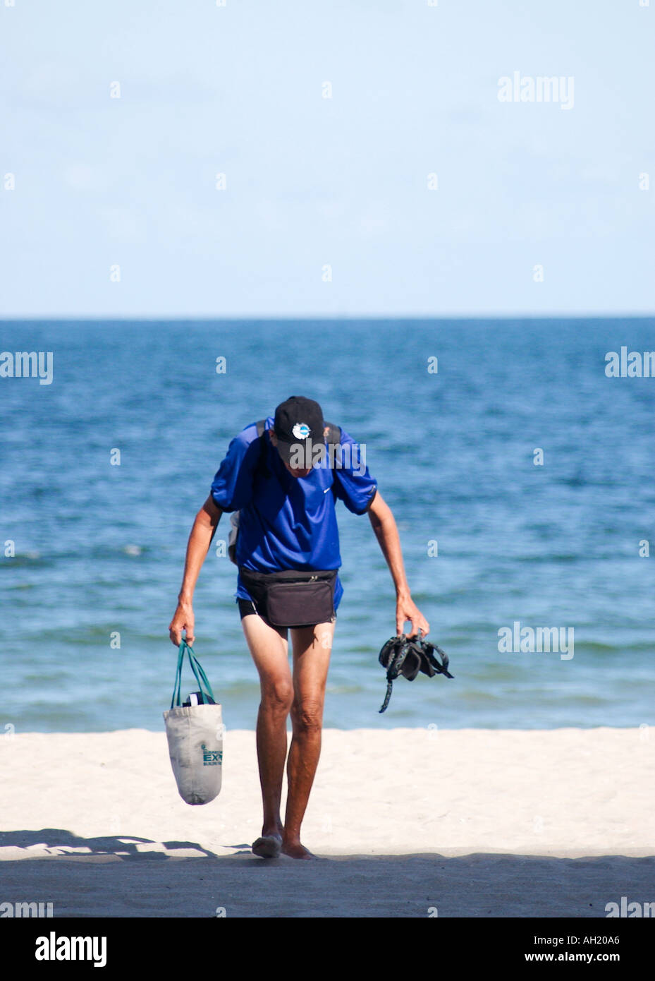 Caucasian Man Wearing Blue Shirt Black Shorts Comes in From Day of Recreation at the Beach Ft Lauderdale Florida Stock Photo