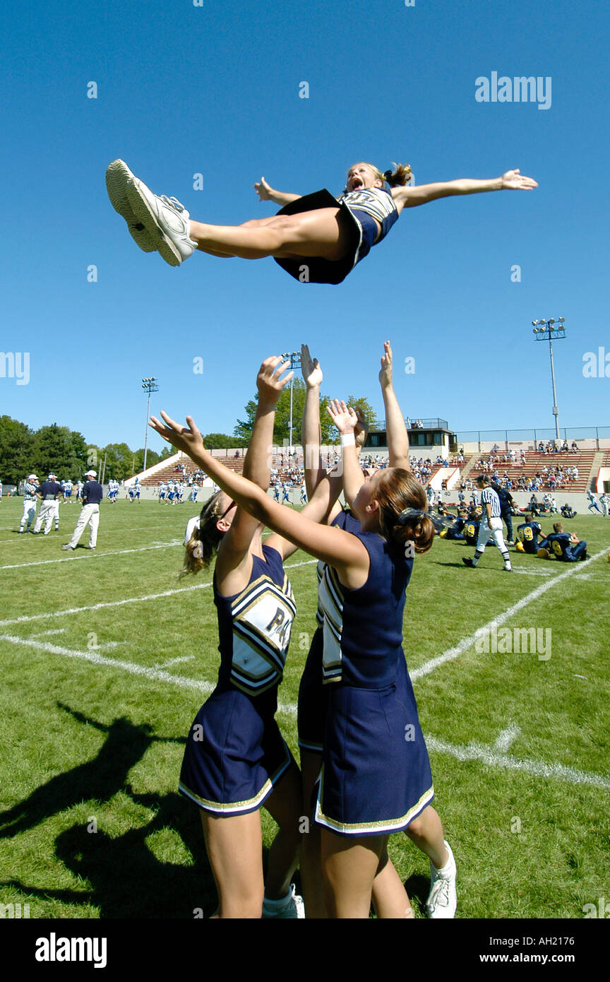 Cheerleaders Perform During Football Game risking injury - Stock Image