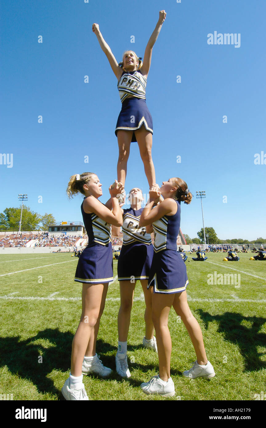 Cheerleaders Perform During Football Game risking injury - Stock Image