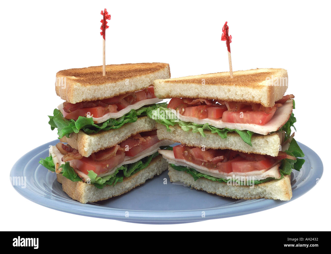 Club sandwich with toothpicks on plate silhouetted on white background - Stock Image