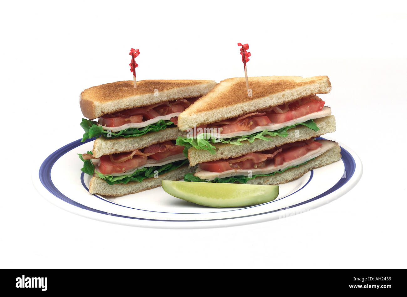 Club sandwich with a pickle on plate silhouetted on white background - Stock Image