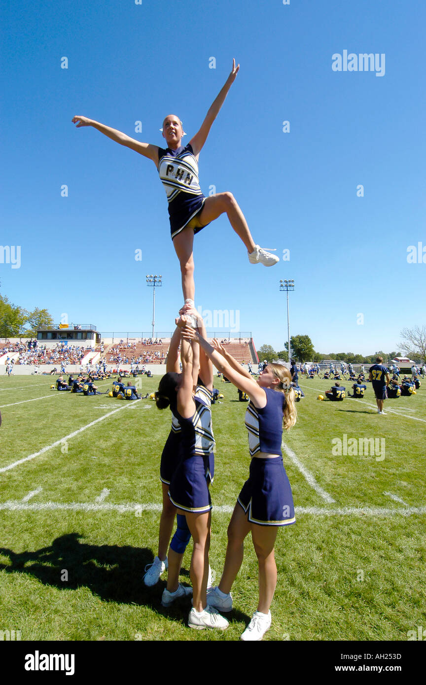 Cheerleaders Perform During High School Football Game - Stock Image