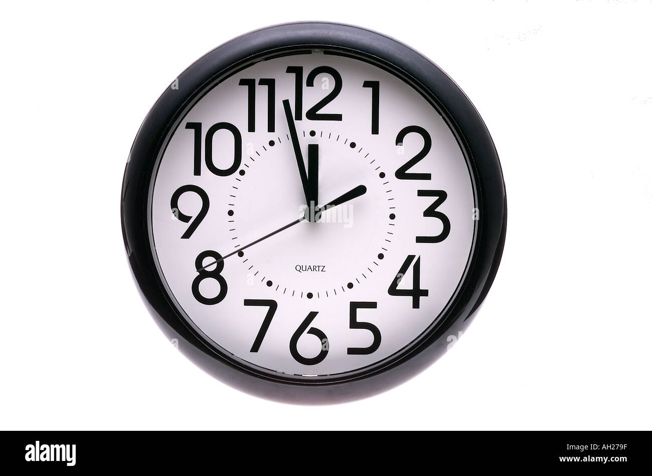 wall clock eleven fifty eight 11 58 silhouetted on white background - Stock Image