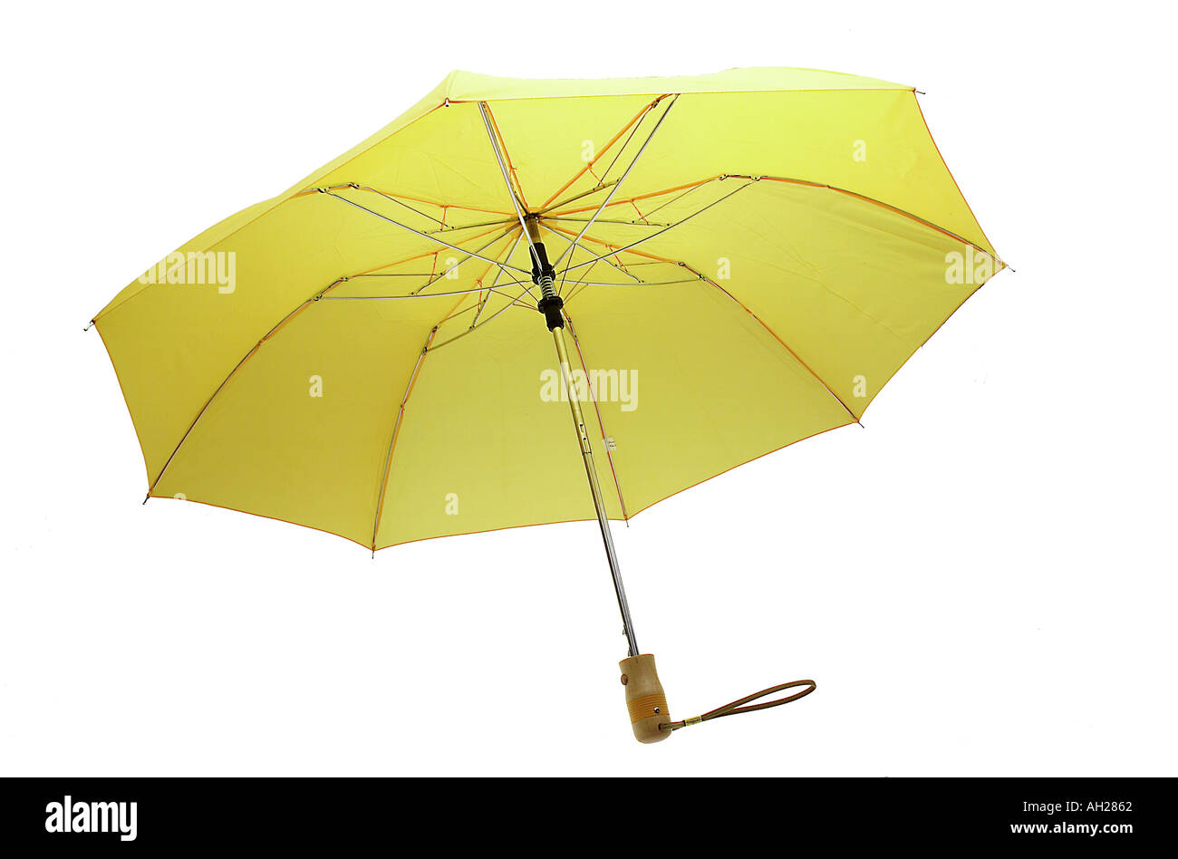 Yellow umbrella silhouetted on a white background - Stock Image