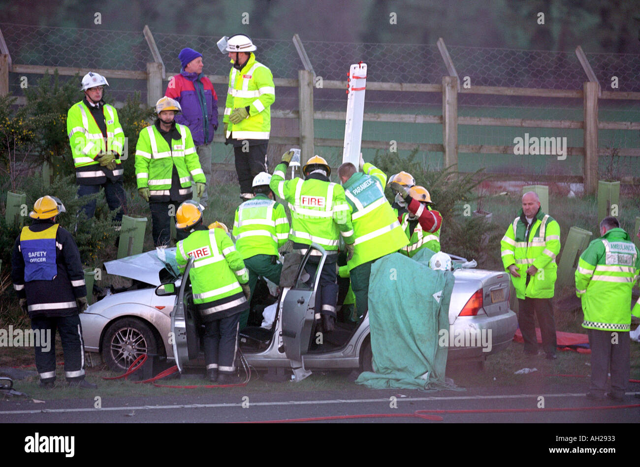 Firefighters cut free a victim of a road traffic accident Stock Photo