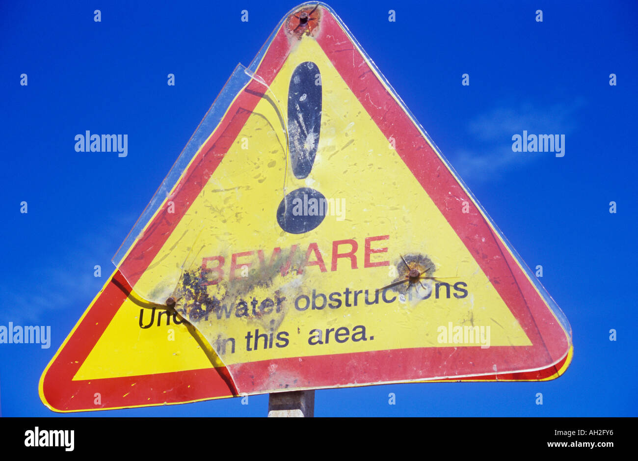 Battered triangular red yellow and black sign against bright blue sky stating Beware Underwater obstructions in Stock Photo