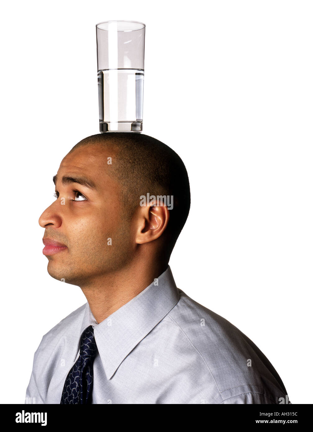 African American Man with glass of water on head - Stock Image