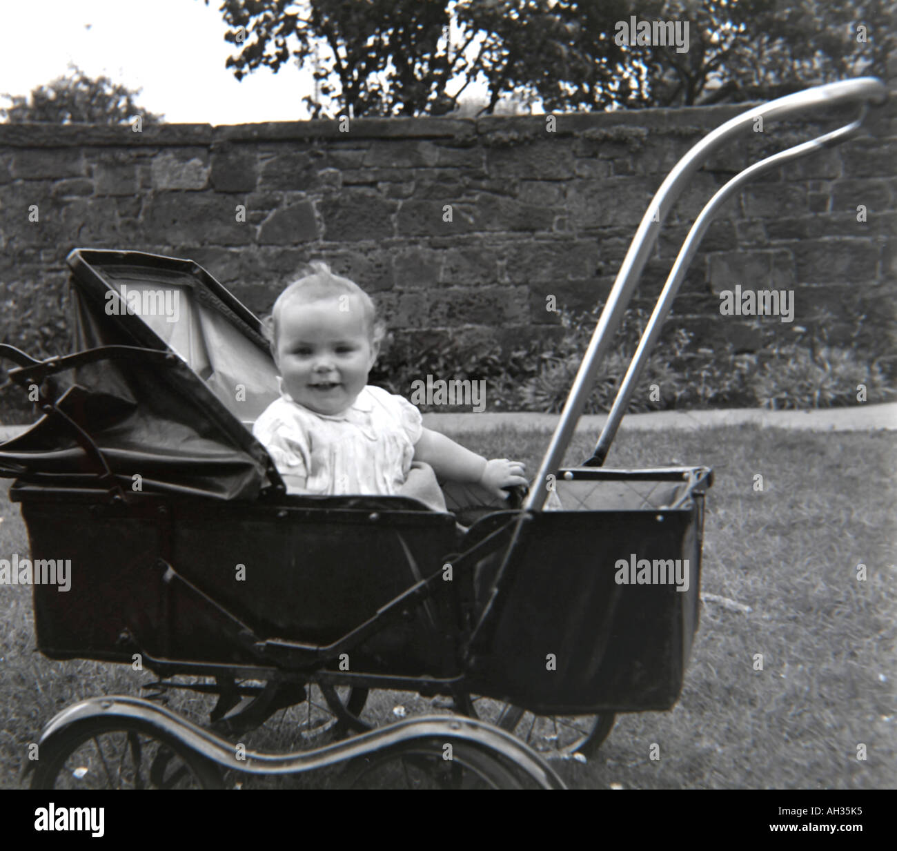 OLD VINTAGE FAMILY SNAPSHOT PHOTOGRAPH OF BABY SITTING AND SMILING IN FASHIONED PRAM