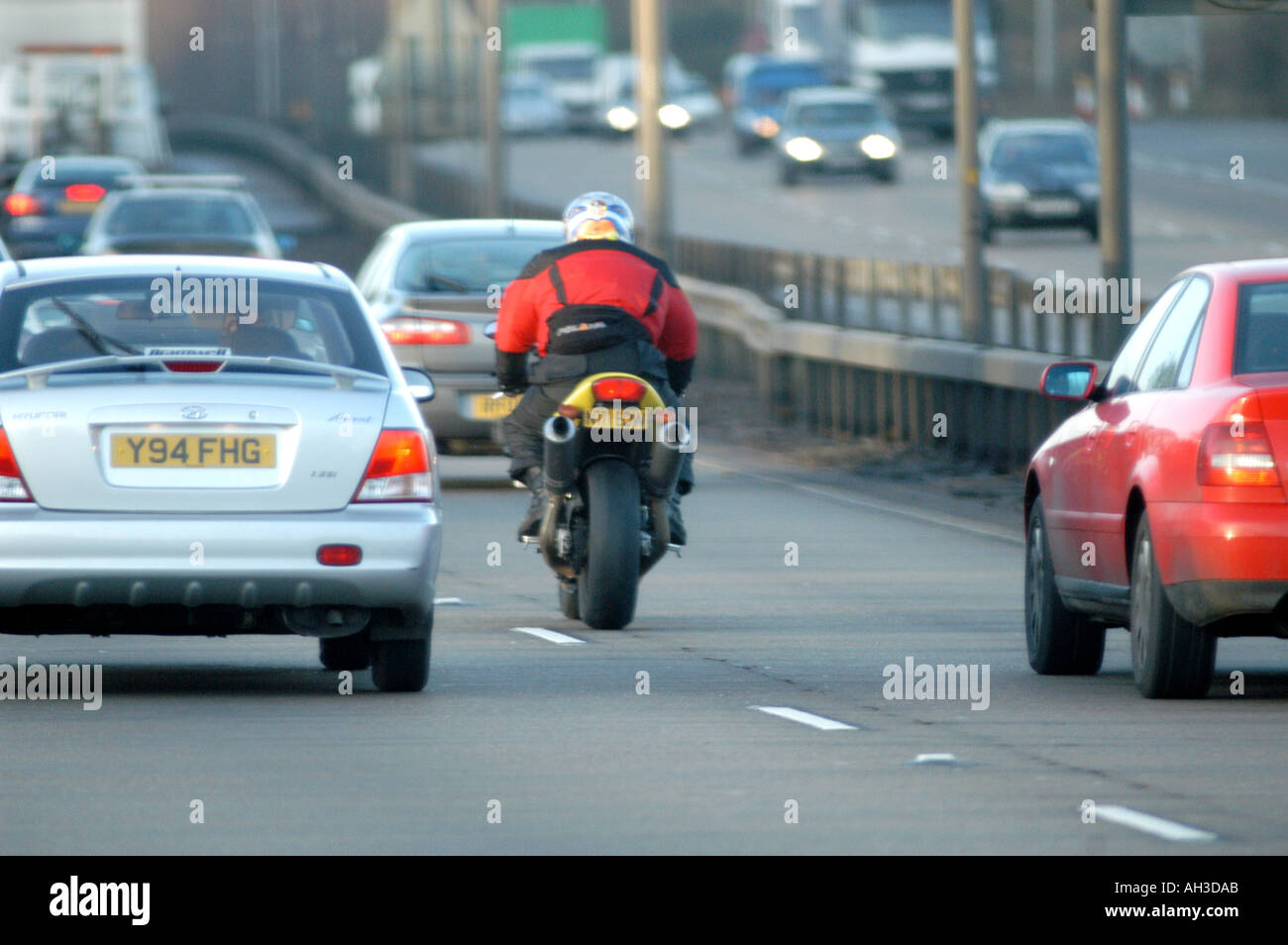 motorcycle cutting through traffic in london  uk - Stock Image