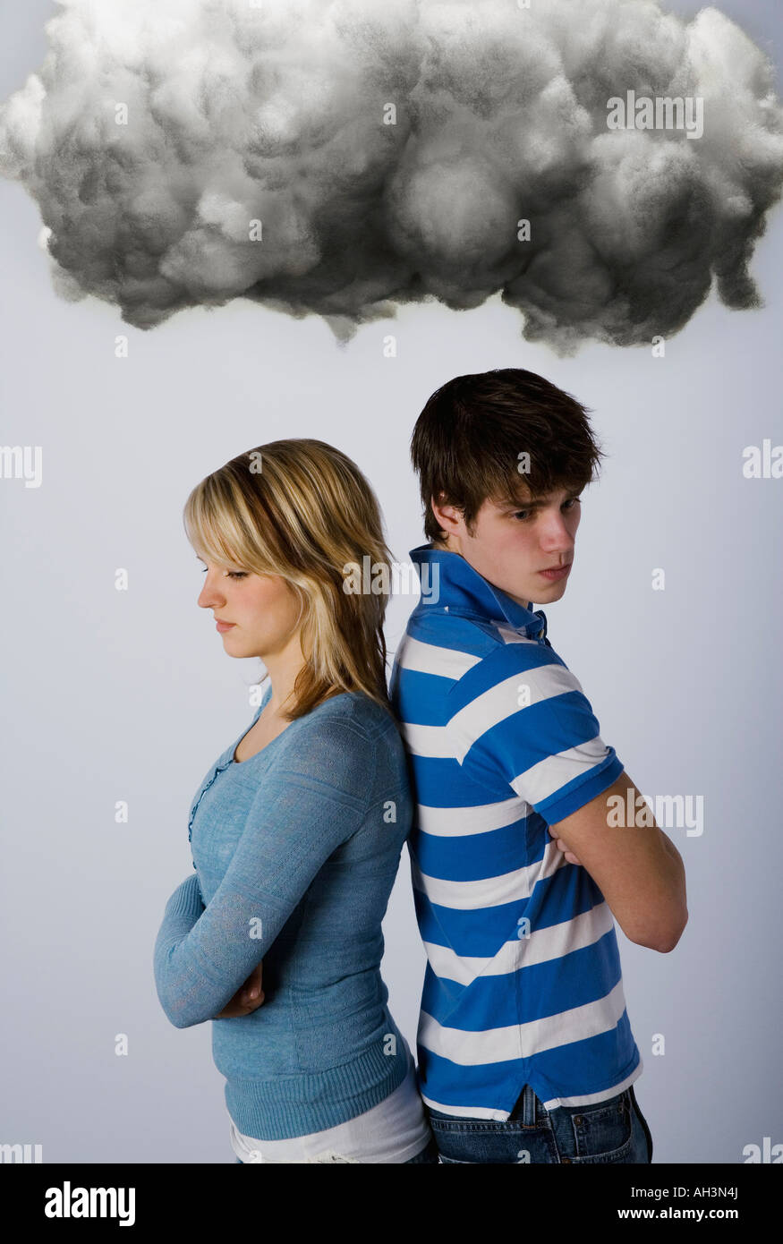 Male and female under dark cloud - Stock Image