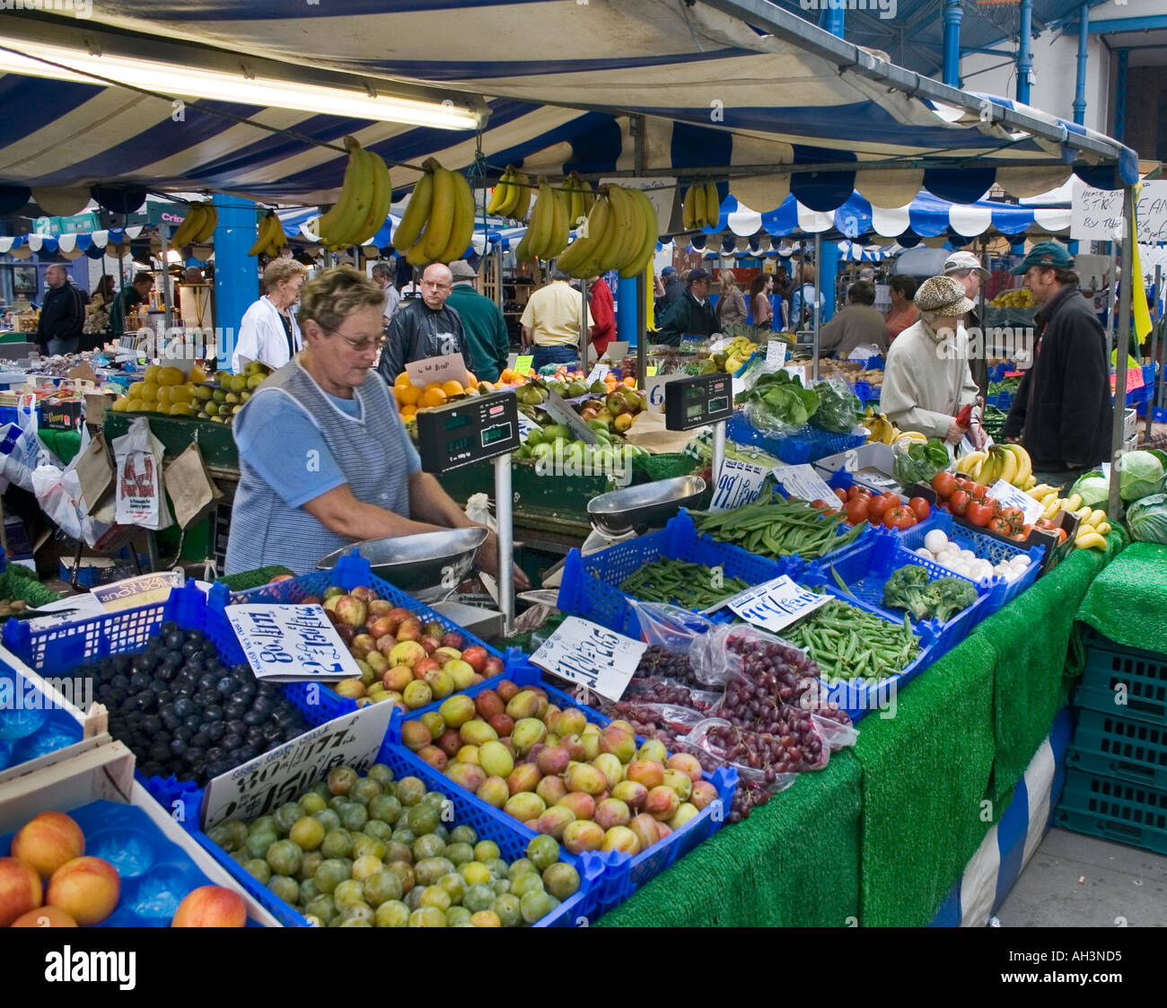Woman selling fruit and vegetables produce priced in imperial and metric money indoor market Abergavenny Wales UK - Stock Image