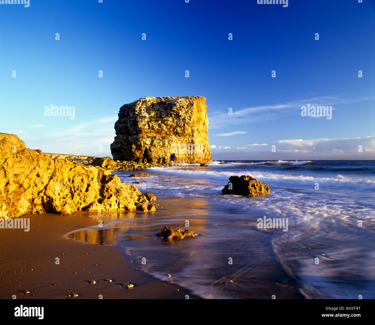 Marsden Rock on South Tyneside, Tyne and Wear at sunrise over a wet beach - Stock Image