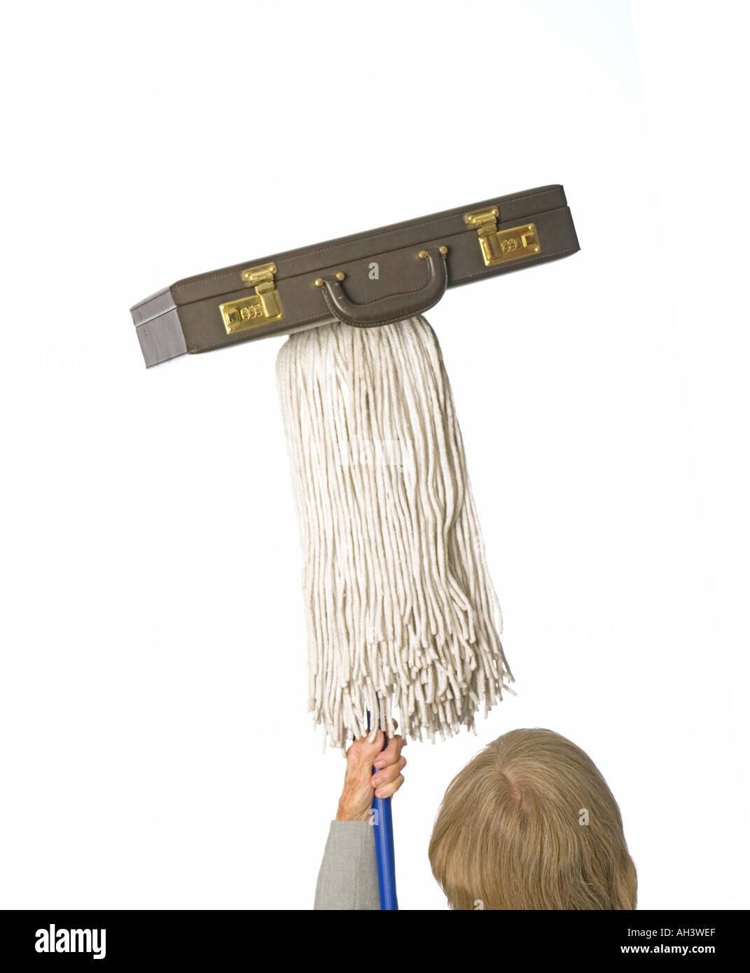 career vs home concept woman balancing briefcase on mop - Stock Image