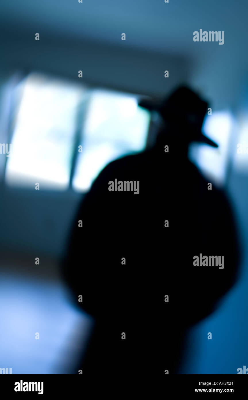 bad guy mystery man silhouetted in blurred room - Stock Image
