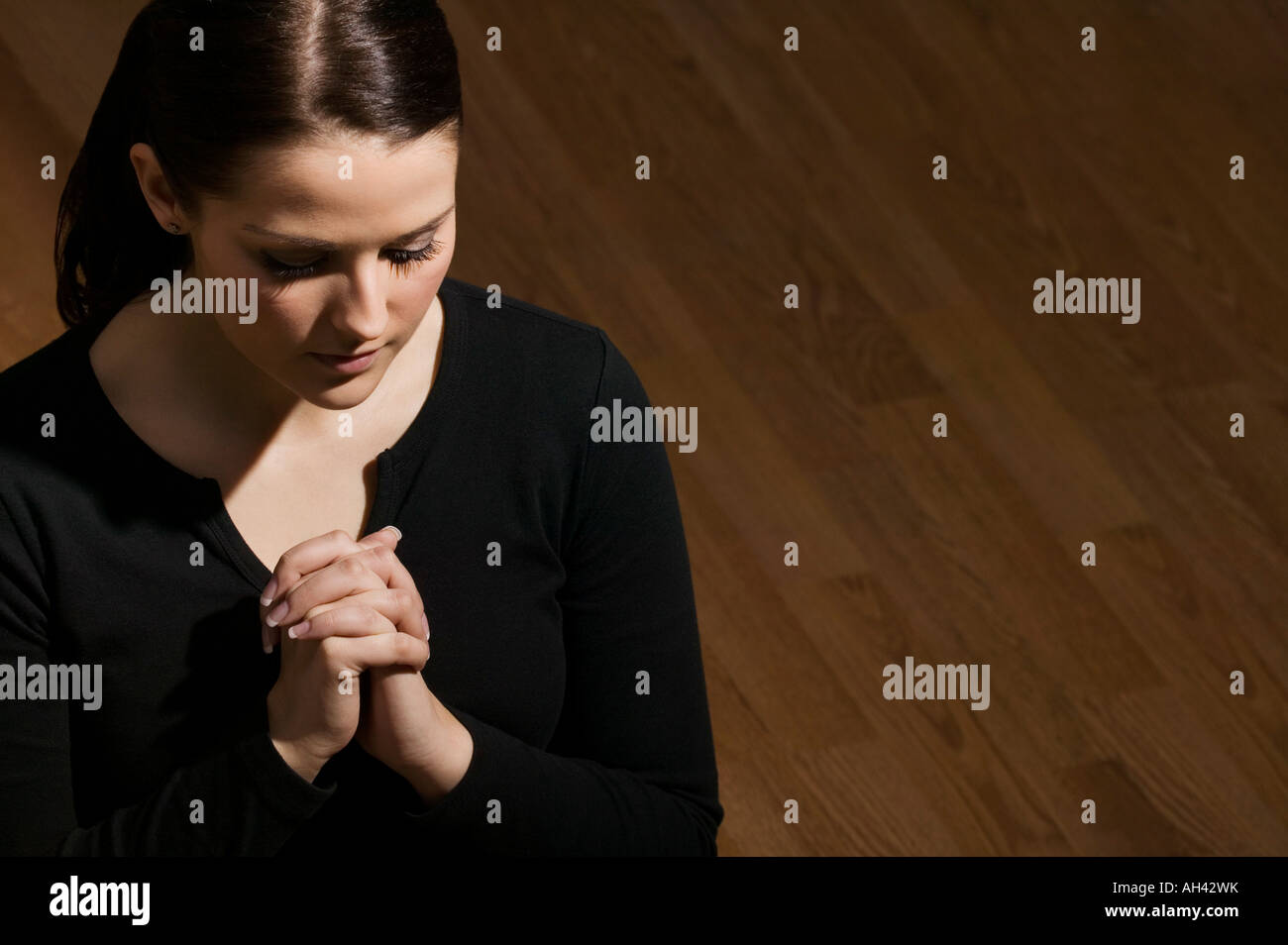 Woman with folded hands and head bowed - Stock Image