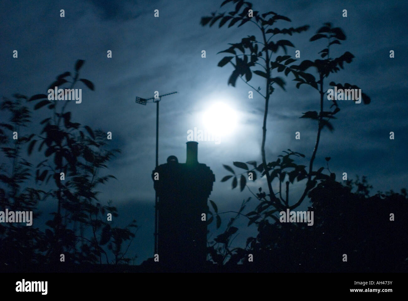 Silouetted Chimney with TV Aerial backlit by full moon with Trees around - Stock Image