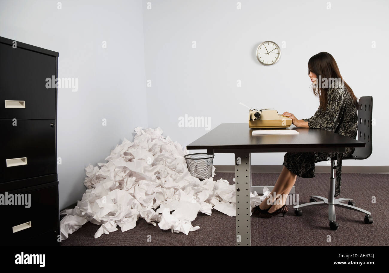 Businesswoman in office with crushed pile of paper on floor - Stock Image