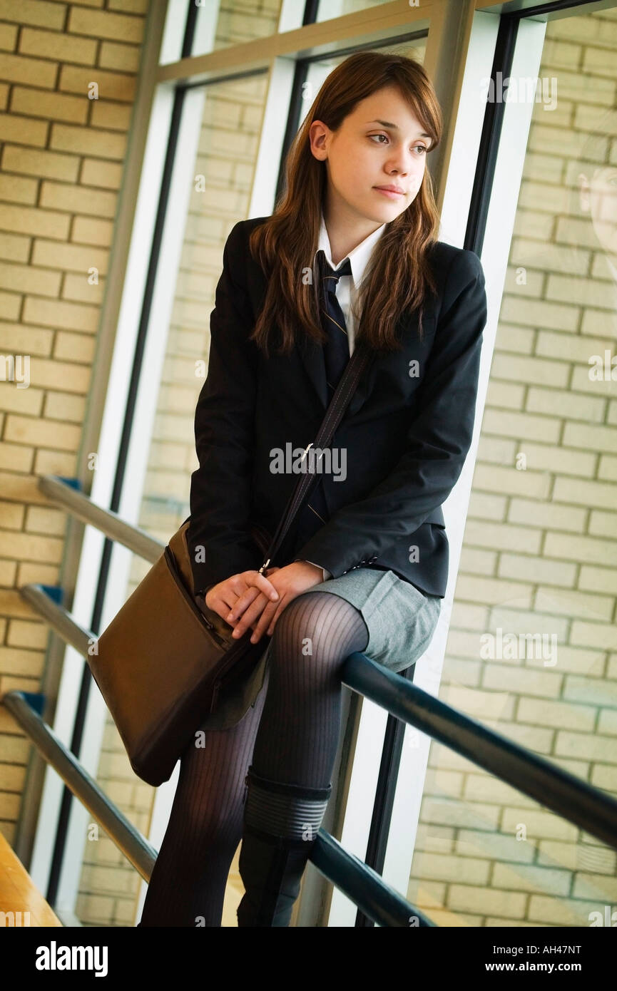 A student in uniform, seated on railing Stock Photo
