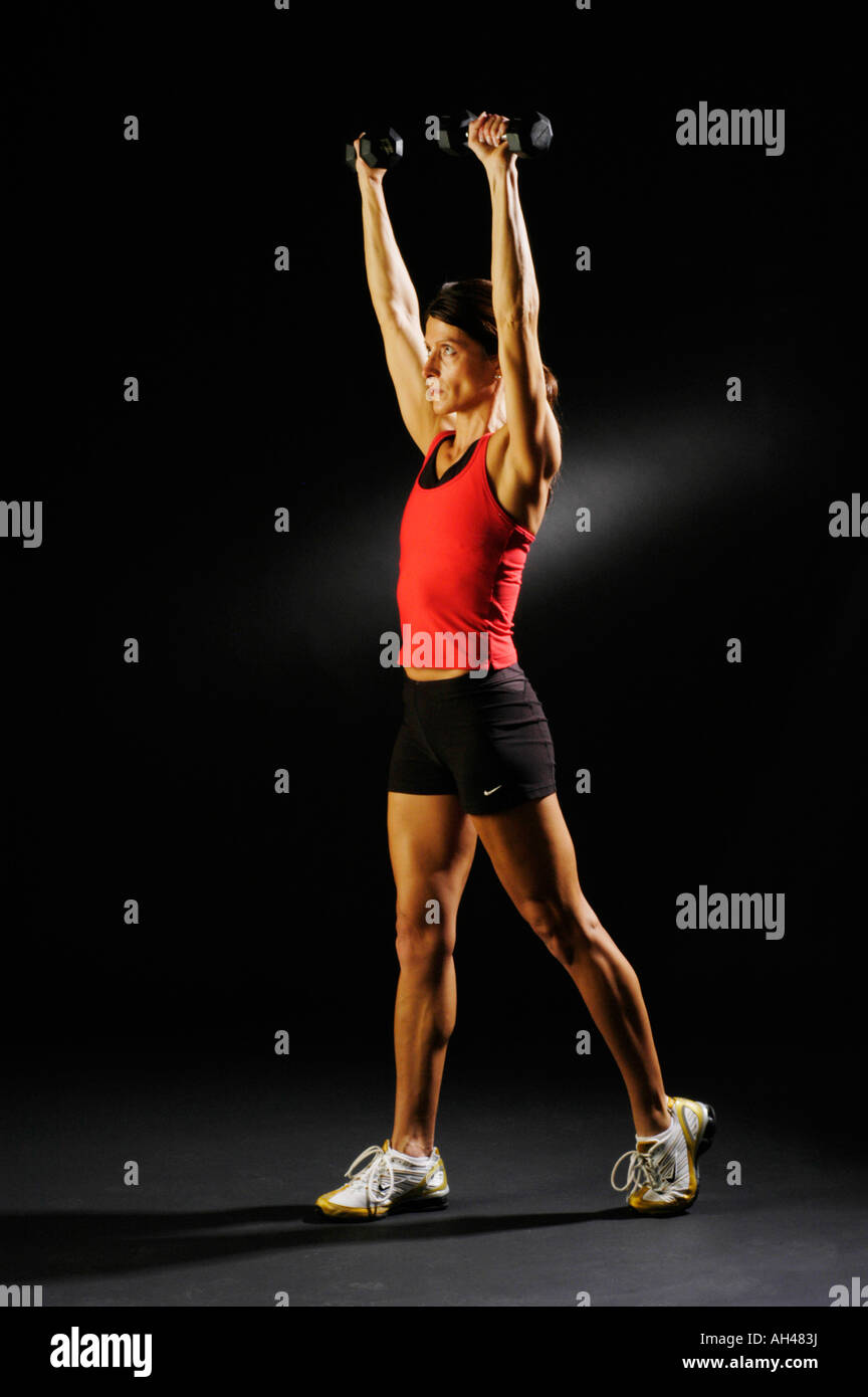 A very fit and muscular women in her 40 s is seen doing standing dumb arm presses as part of her Body Pump class - Stock Image