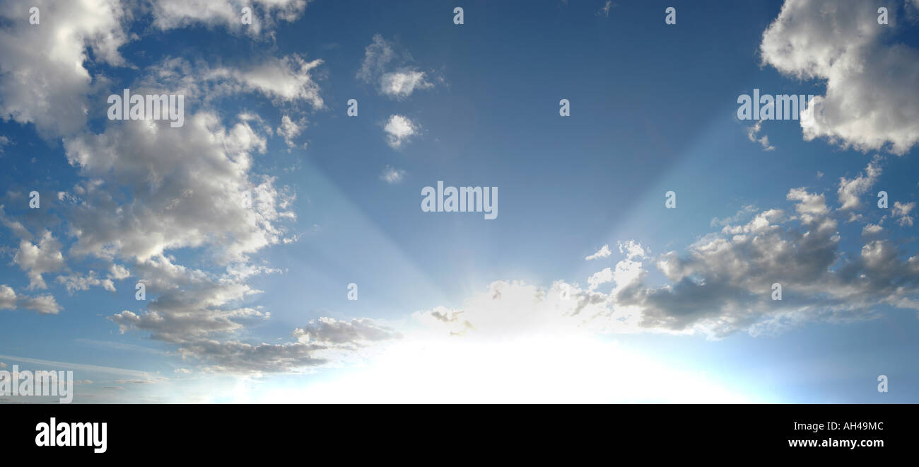 sunrays on a bright blue sky with clouds, Sweden - Stock Image