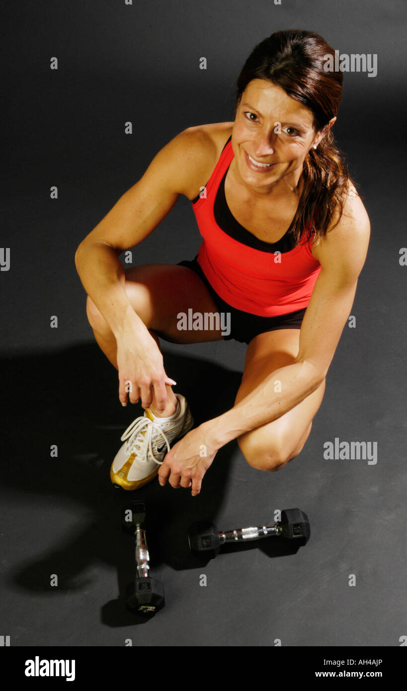 A fit and muscular women in her 40 s is a seen wearing exercises cloths squatting next to dumb bells in front of - Stock Image