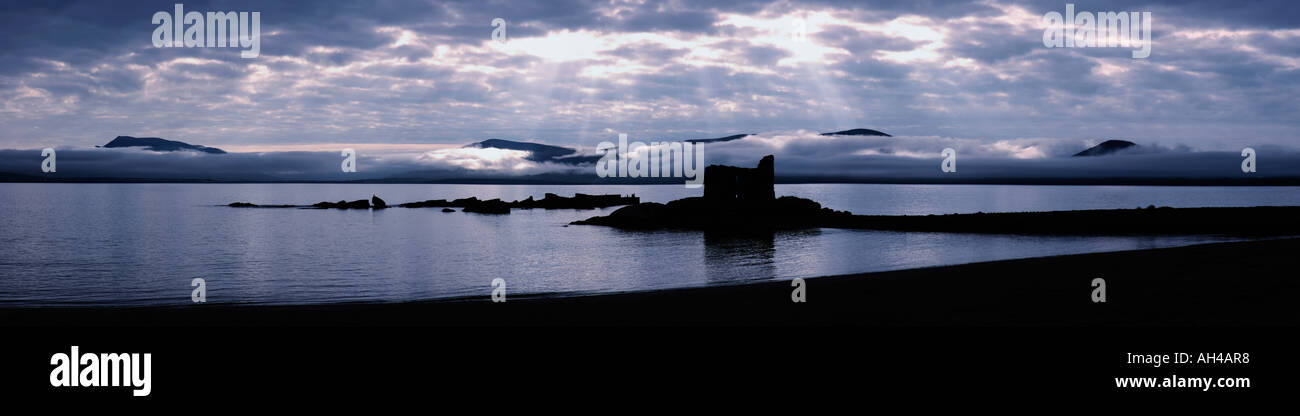 sunbeams over ruins/lighthouse built in stone, West coast, Ireland - Stock Image