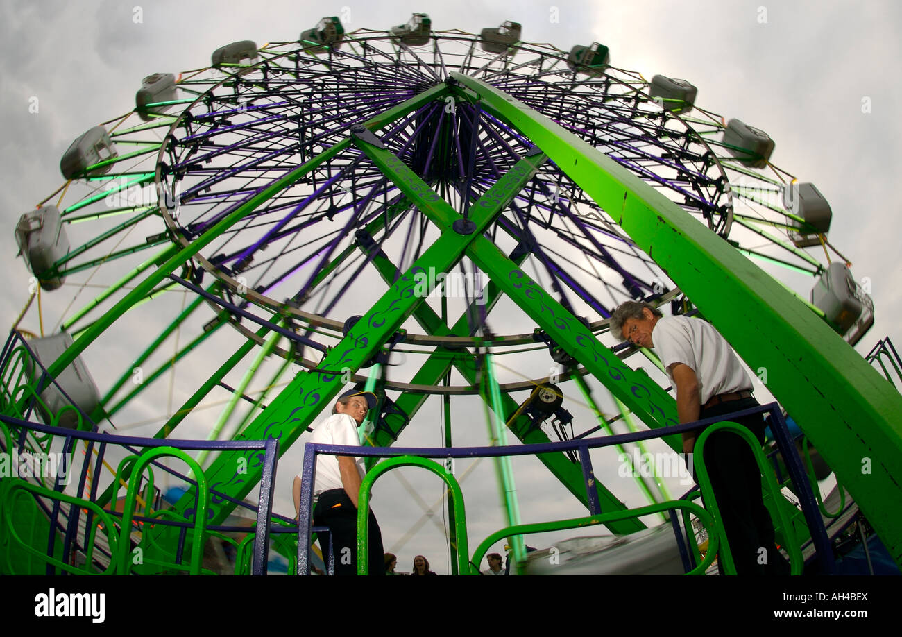 Carnival employees operate the Skydiver ferris wheel on a ...