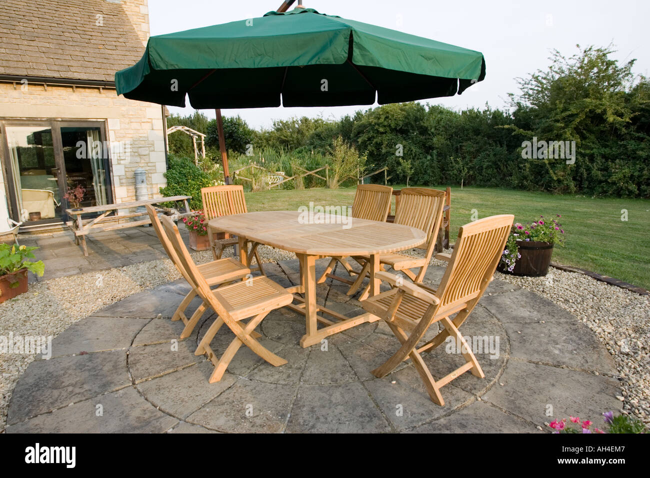 Teak Garden Table And Chairs On Patio With Large Umbrella Above Cotswolds UK