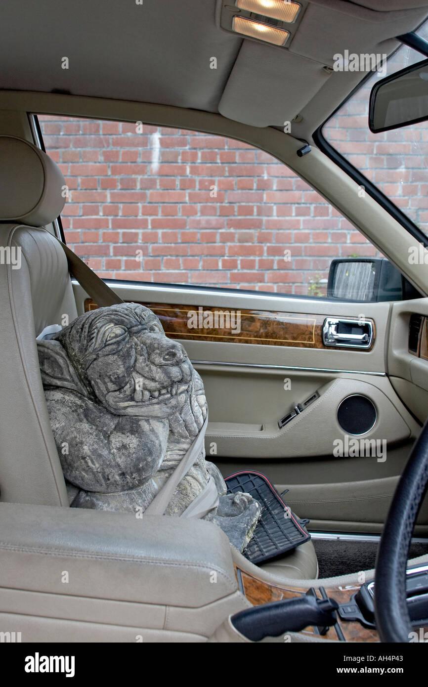 Strange funny amusing monster hitch hiker passenger in car - Stock Image