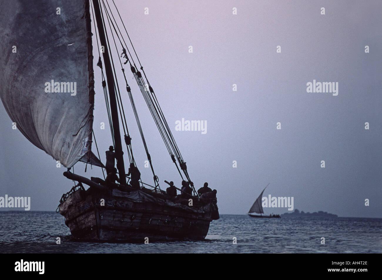 Cargo laden dhow approaching Stone Town at dusk Unguja Zanzibar Tanzania East Africa - Stock Image