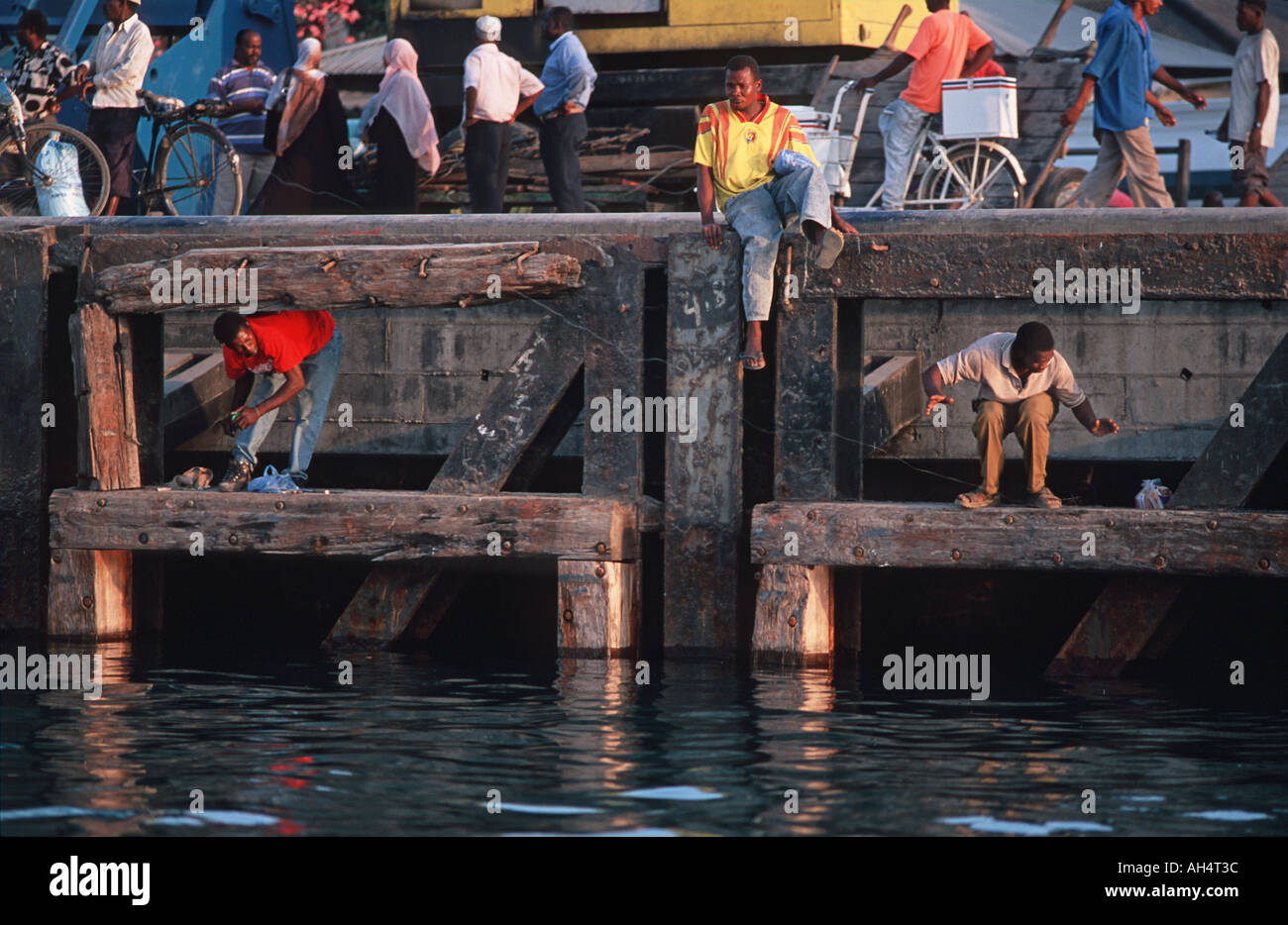 Men fishing with lines at the waterfront beside the harbour Stone Town Zanzibar Tanzania East Africa Stock Photo