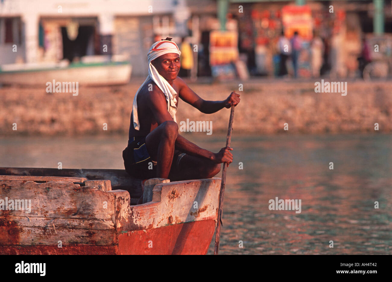 Fisherman in boat at sunset Stone Town waterfront Zanzibar Tanzania East Africa - Stock Image