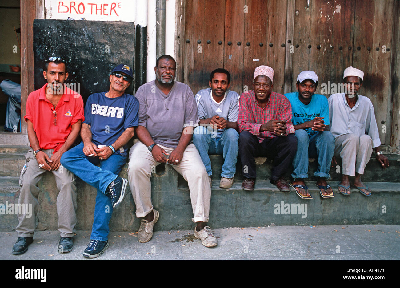 Gathering of men at Jaws Corner for lively political debate and to share coffee and friendship Stone Town Zanzibar Tanzania - Stock Image