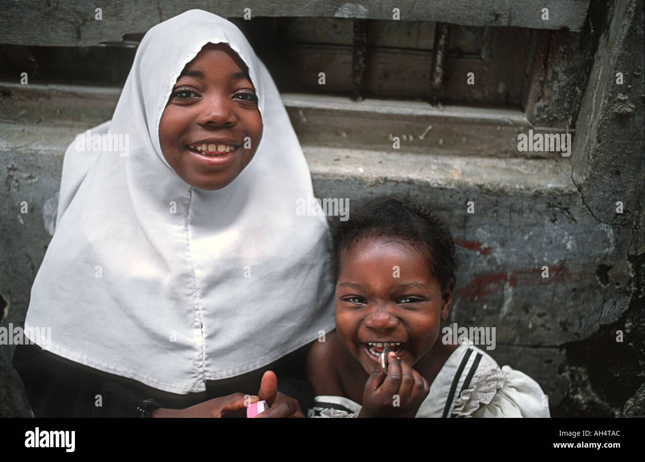 Happy Zanzibari girl wearing a muslim headcloth and her younger sister Stone Town Zanzibar Tanzania East Africa - Stock Image