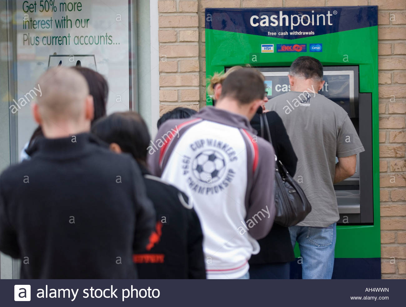 migrant workers queueing up to withdraw their wages from a cashpoint machine in Thetford, Norfolk - Stock Image