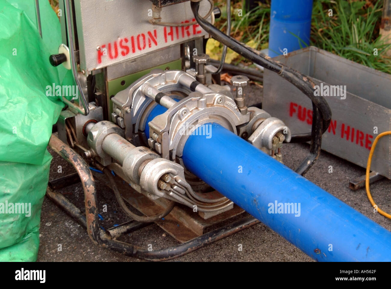 Brentwood blue plastic water main pipes in welding machine to make continuous length of pipe prior to installing below road & Brentwood blue plastic water main pipes in welding machine to make ...