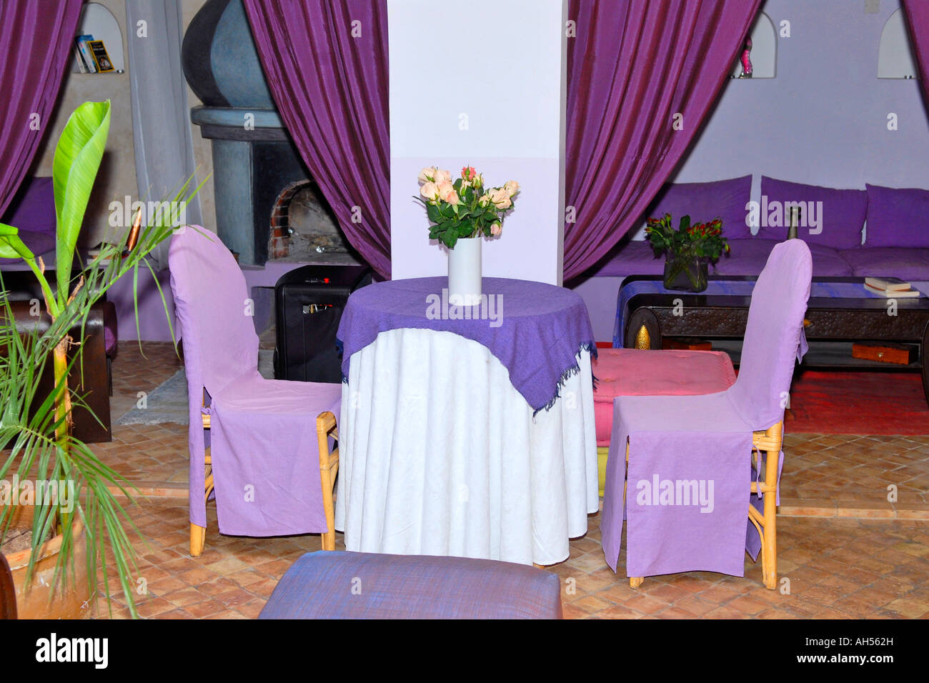 Morocco , Essaouira , Riad El Madina hippy hotel , typical African courtyard with mauve lounge settees , drapes - Stock Image