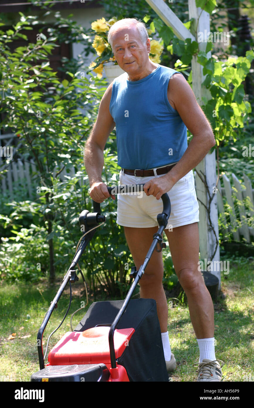 outdoor summer garden day bush bushs man 50 55 smile smiling grey haired shirt blue stand shorts white mower cut grass vertic - Stock Image