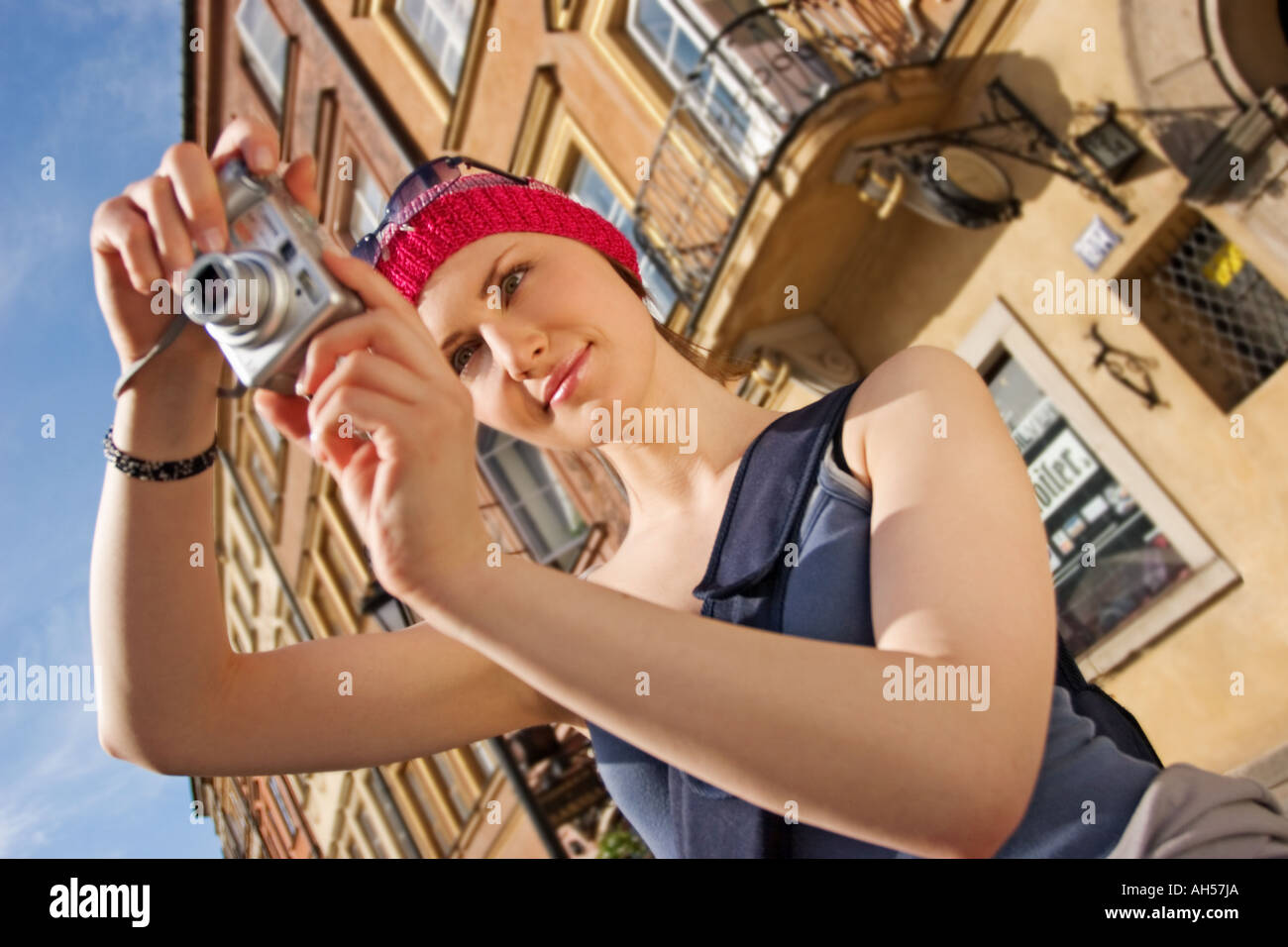 outdoor day summer building buildings architecture tenement tenements young woman 25 30 cap sunglasses dark smile smiling tou - Stock Image