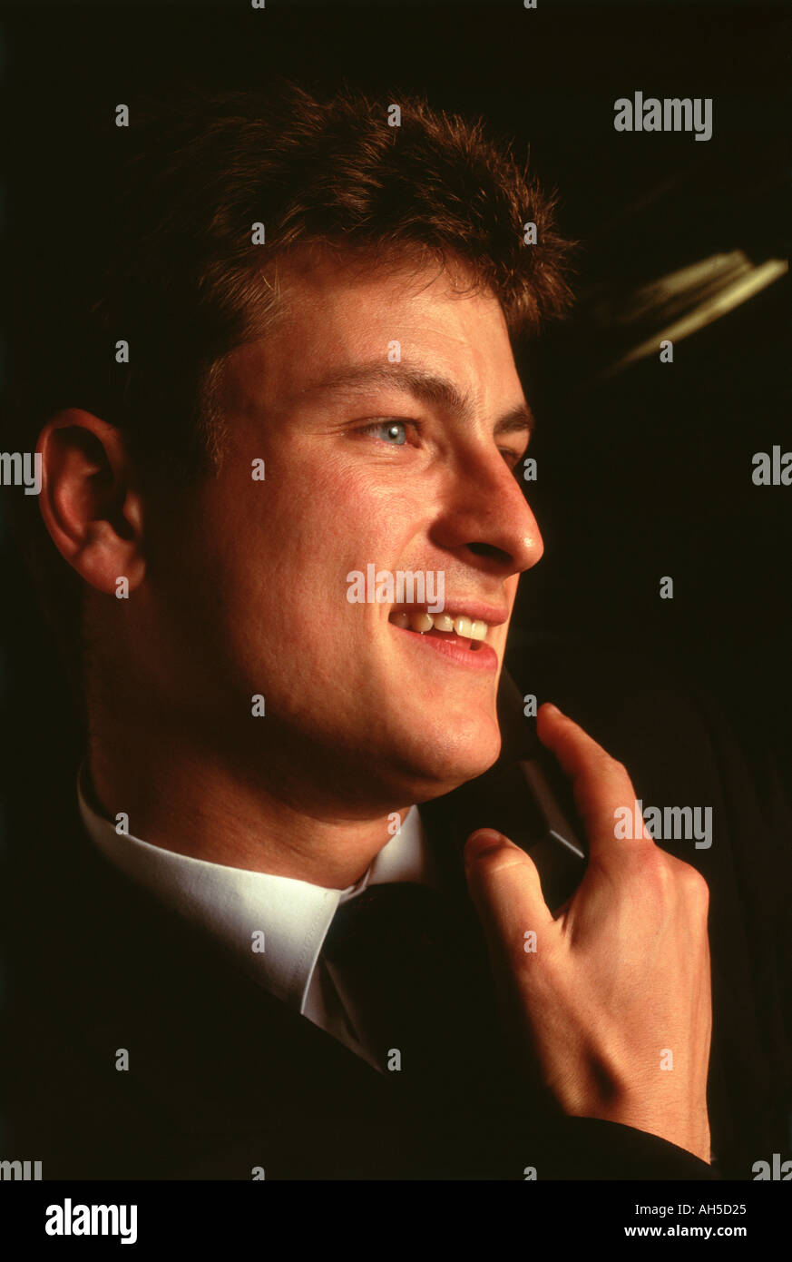 Male receptionist on telephone smiling  - Stock Image