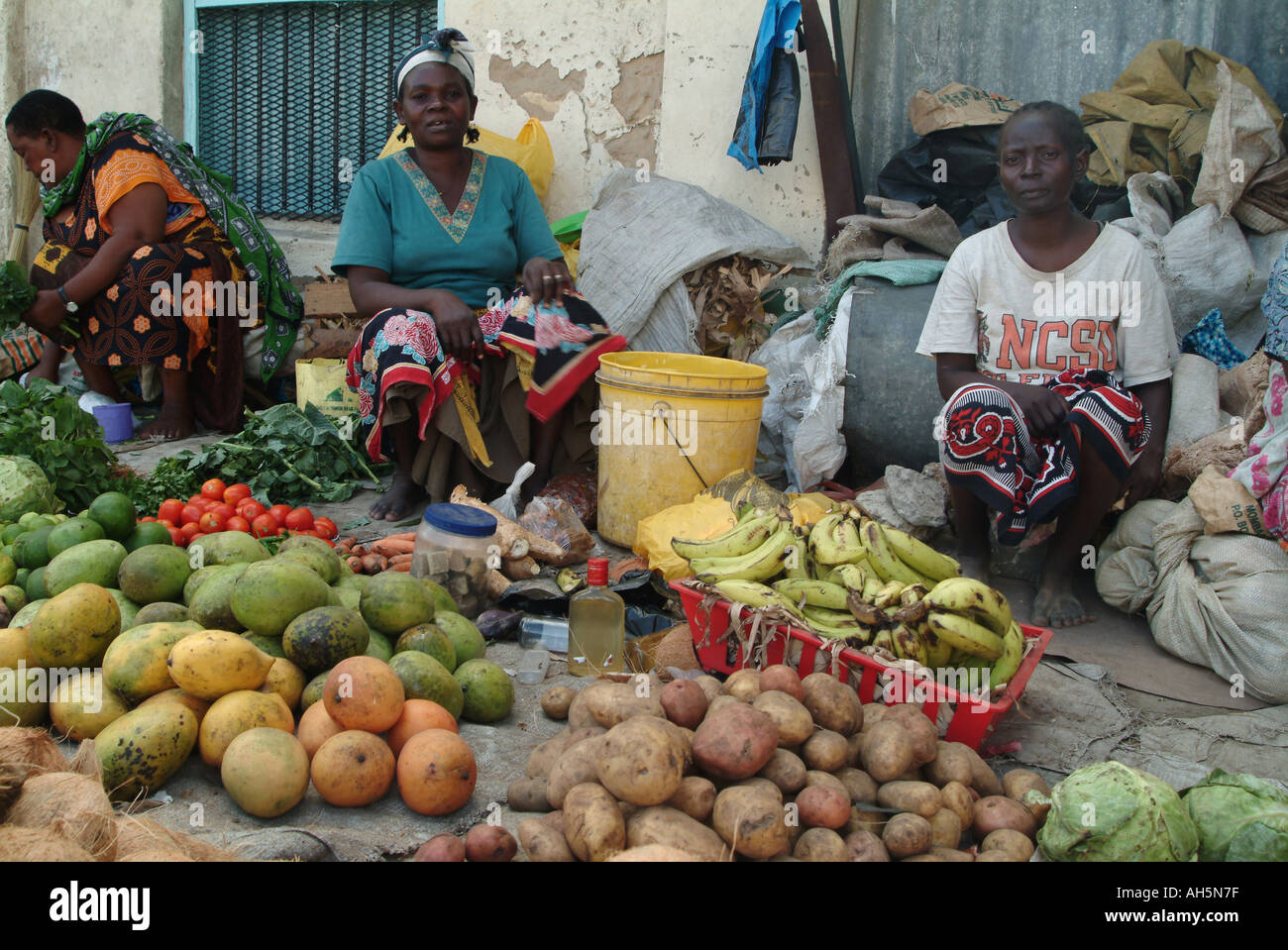 Women selling fruit and vegetables on the pavement in Kenyan