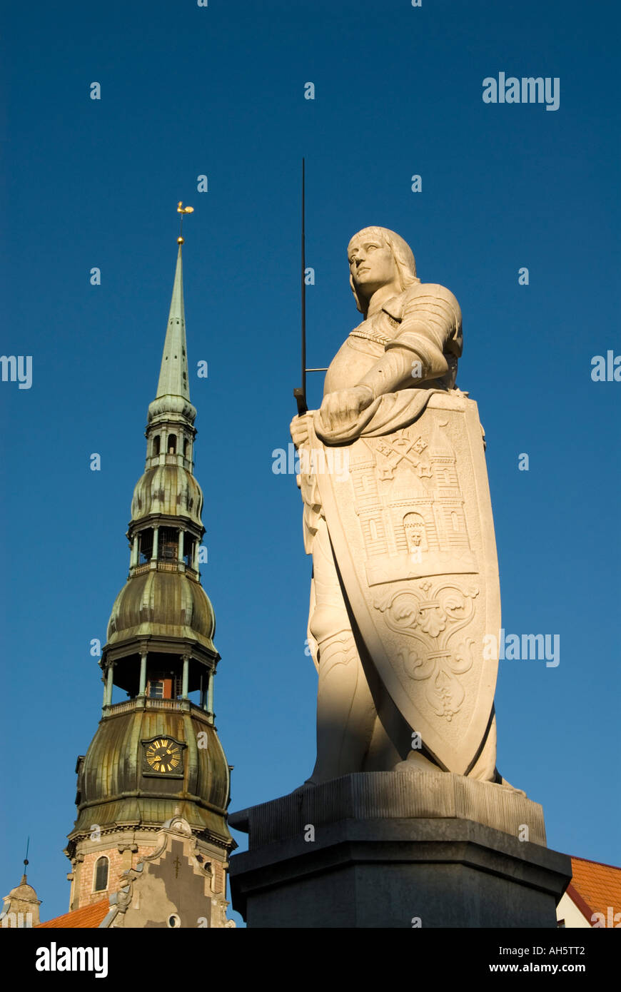 Statue of Roland on Ratslaukums in front the spire of St Peter's Church Riga Latvia - Stock Image