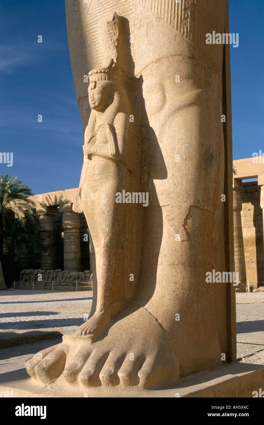 Statue of wife at the feet of Ramses II Ramses the Great Temple of Karnak UNESCO World Heritage Site Luxor Egypt Stock Photo