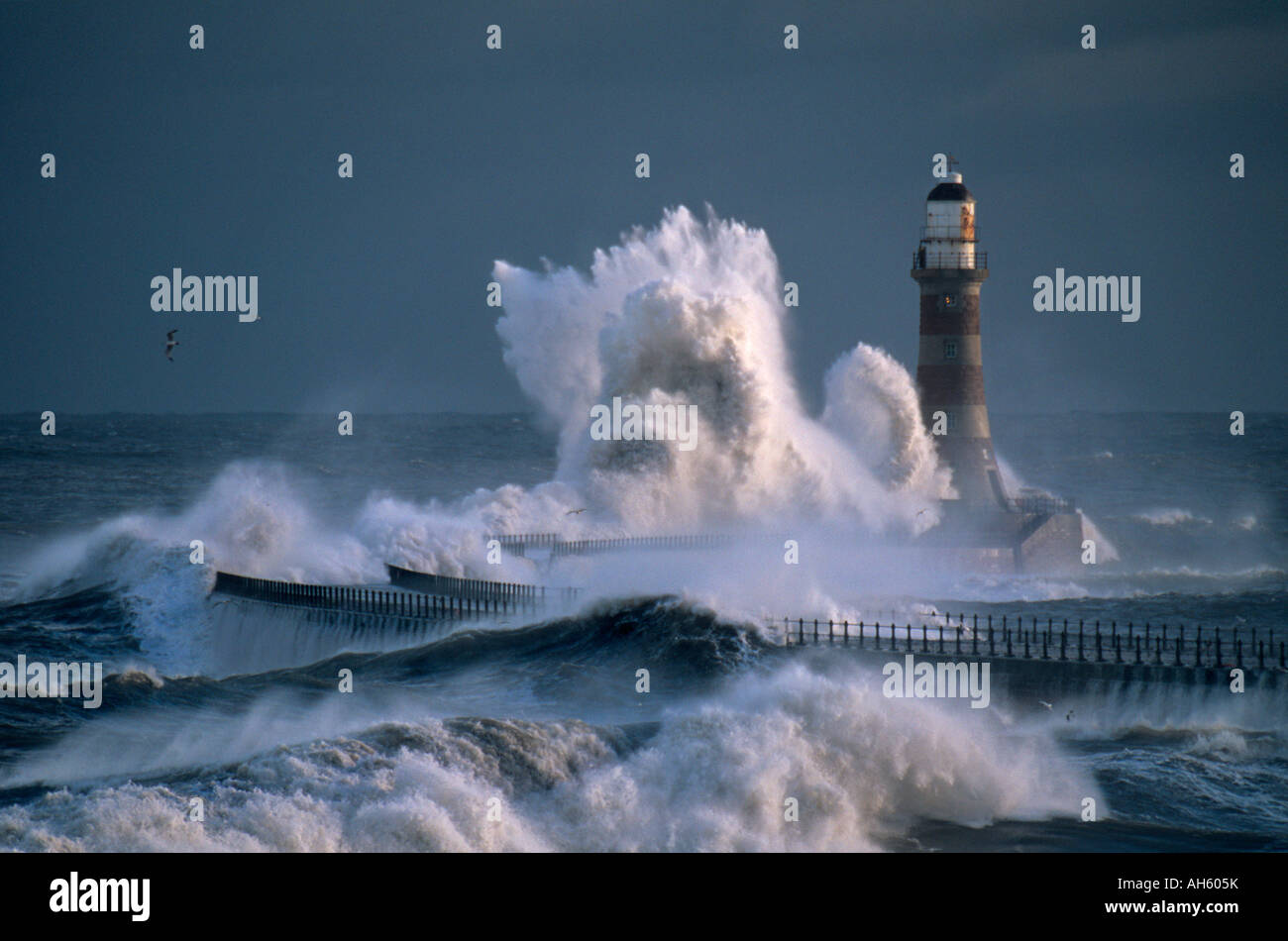 A huge wave breaks over the lighthouse on Roker Pier, during a winter storm. Sunderland. Tyne & Wear. Stock Photo