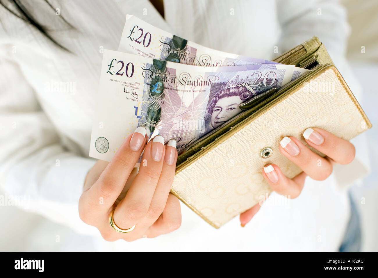 Woman with 20 pound notes in purse - Stock Image